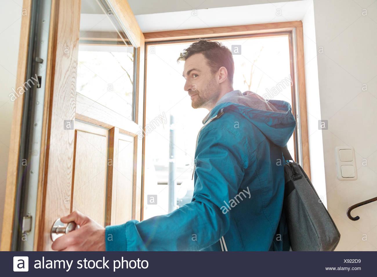 Man leaving front door of house - Stock Image