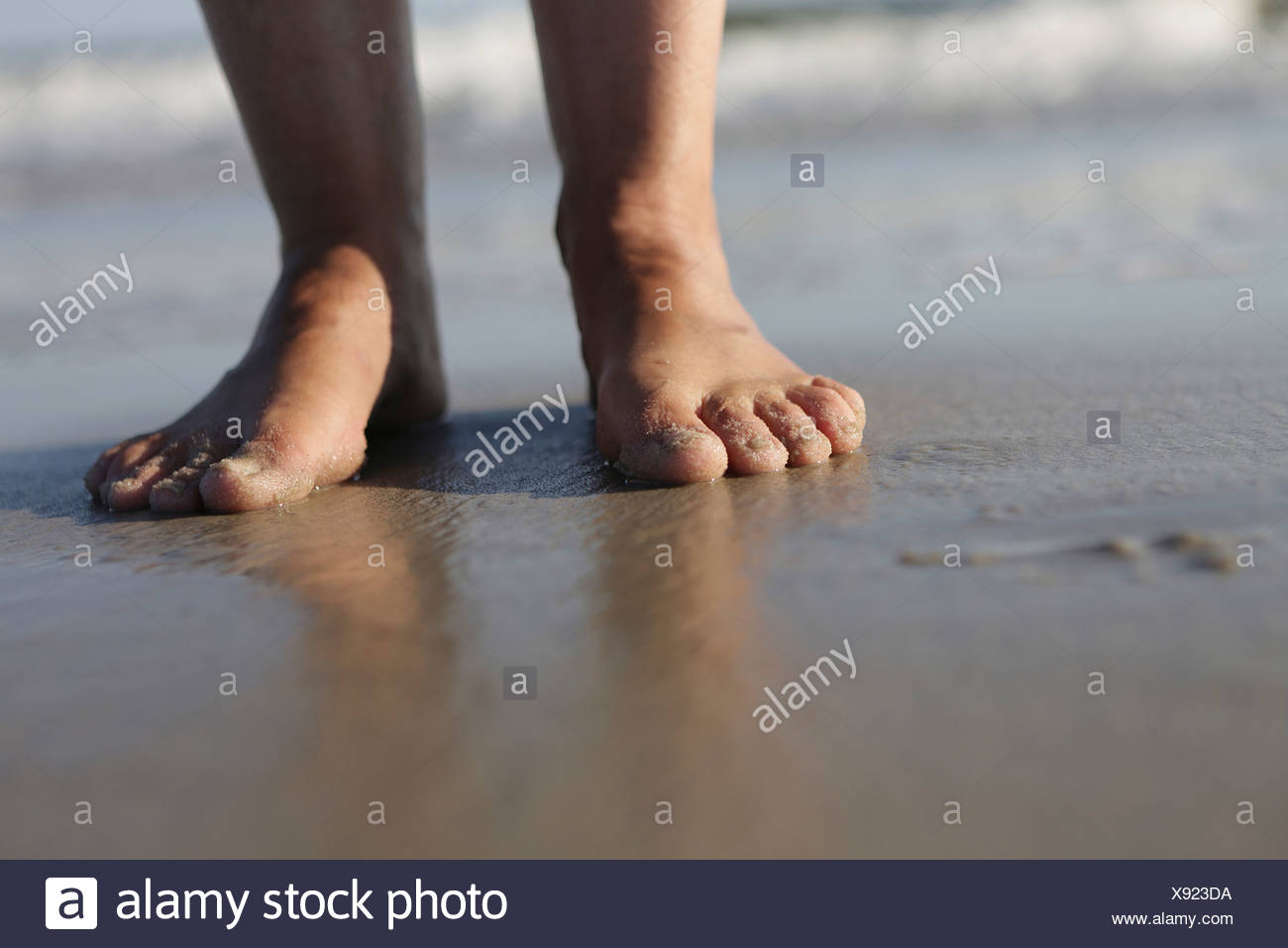 Germany, Lower Saxony, East Frisia, Langeoog, feet of a woman at the beach - Stock Image
