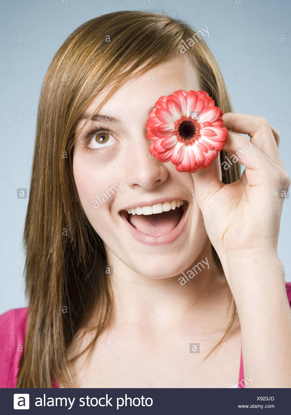 Close-up of woman smiling holding flower up to her eye - Stock Image