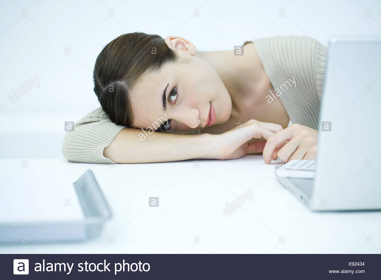 Young woman sitting at desk with head down on arm - Stock Image