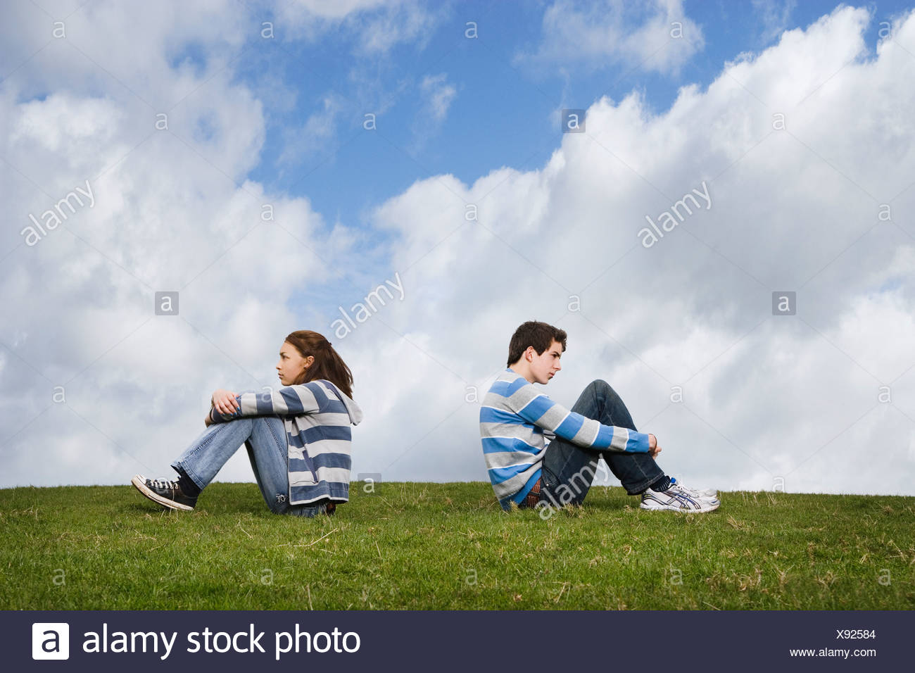 Teenage couple turned away from one another in field Stock Photo