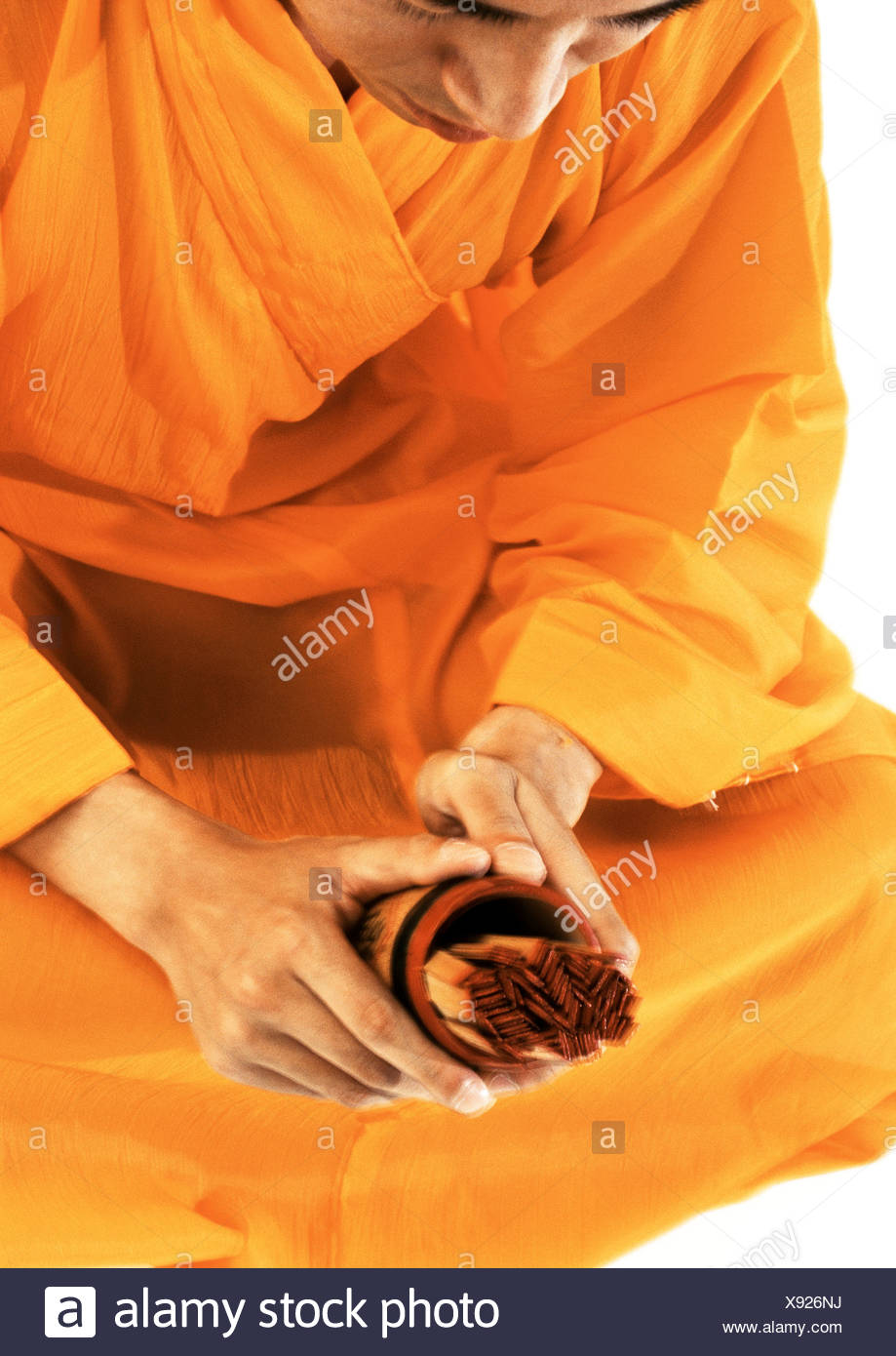 Buddhist monk meditating, holding devotional objects - Stock Image