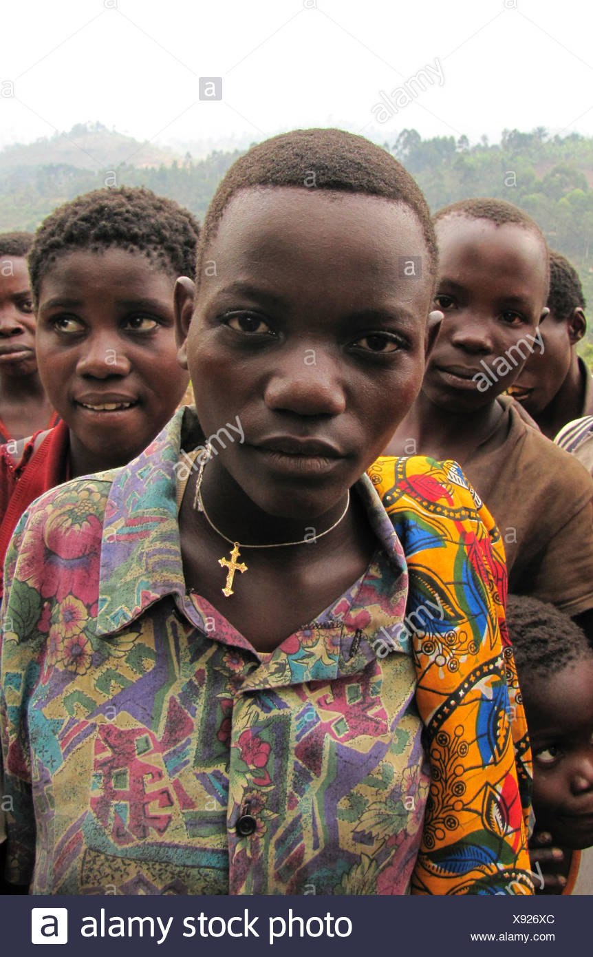 portrait of a girl with a cross on a necklace in front of members of the minority of the Batwa living in an isolated rural area, Burundi, Bujumbura rural, Mutimbuzi - Stock Image