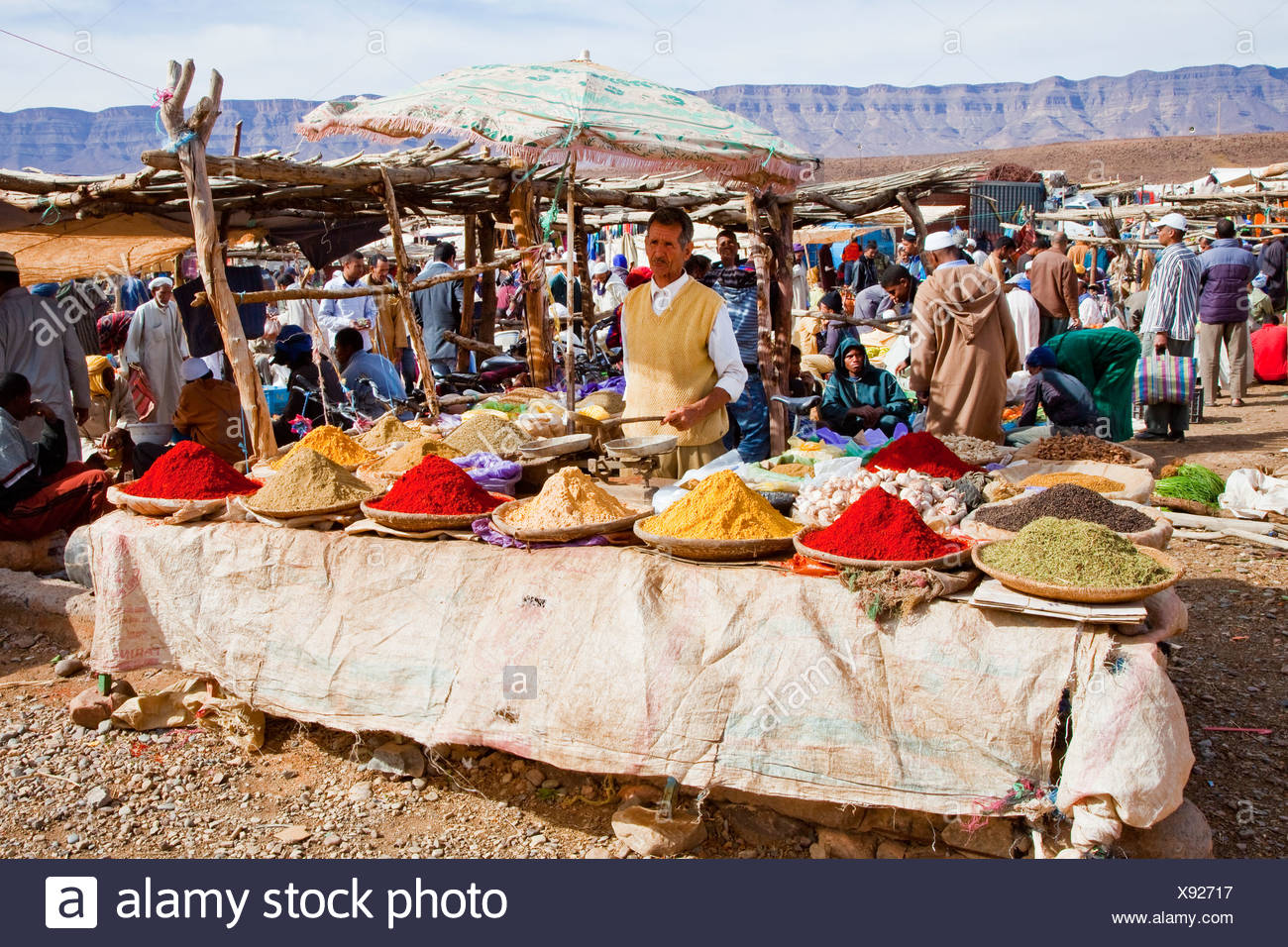 Men wearing Djellabas, traditional robes, with herbs and spices on the market or souq, Tinezouline, Draa valley, Morocco, Africa Stock Photo