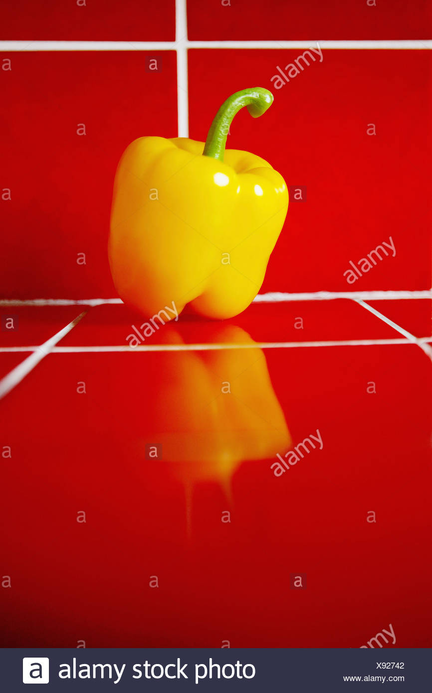 Yellow bell pepper on red tiles - Stock Image
