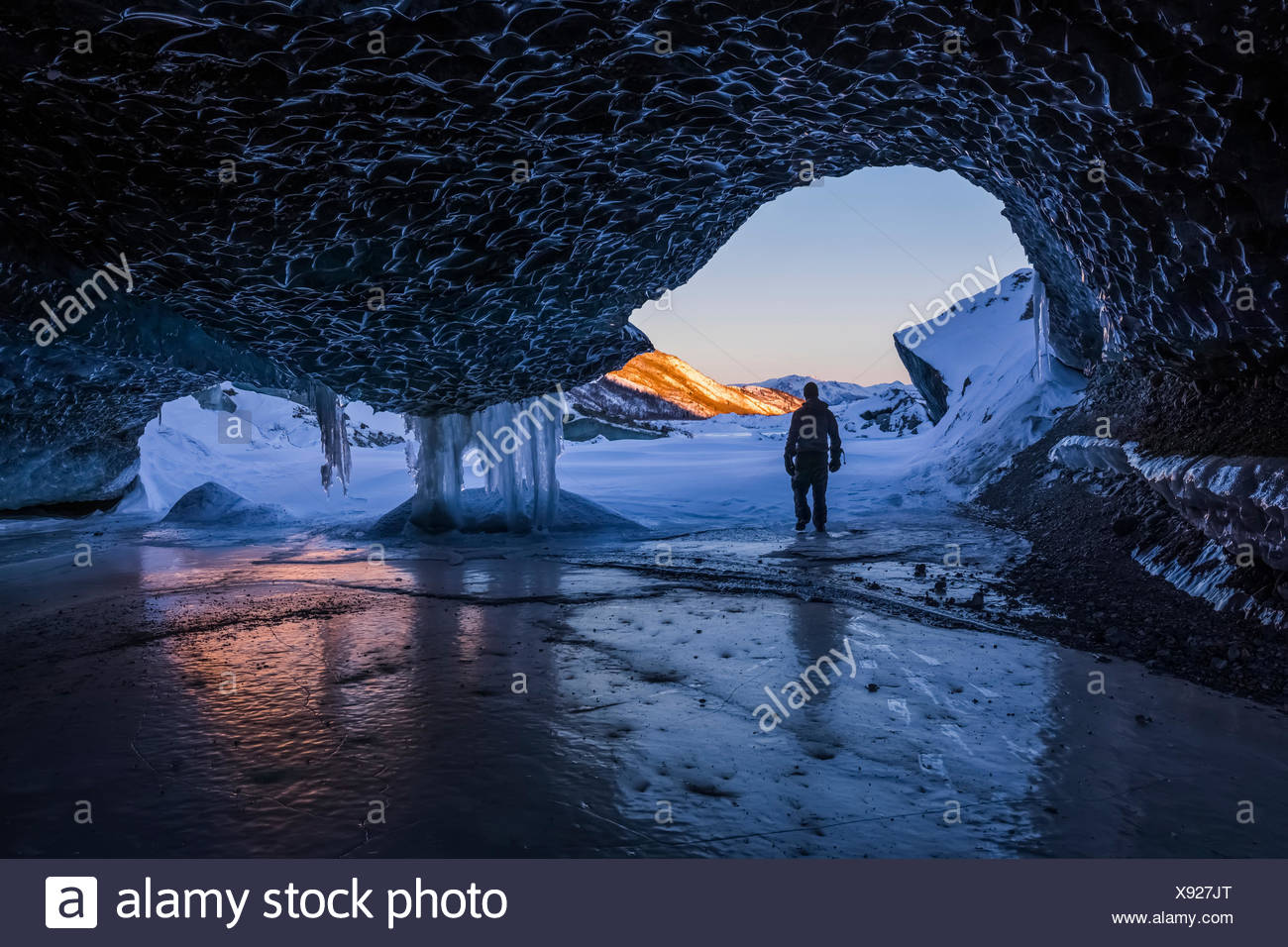 A man walks out the entrance of an ice tunnel at the terminus of Canwell Glacier in the Alaska Range in mid-winter; Alaska, United States of America - Stock Image