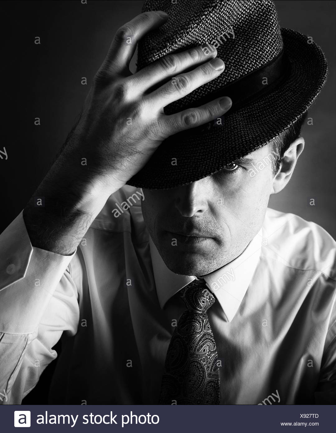 Man with hand on hat - Stock Image