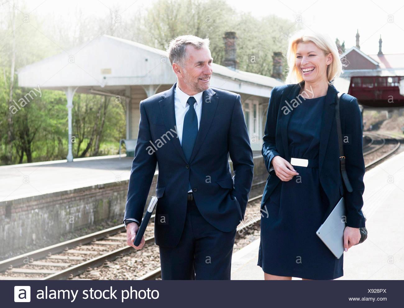 Businessman and woman talking on railway platform - Stock Image