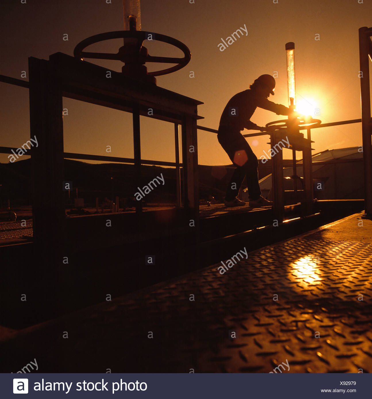 Silhouette of chemical plant worker turning valve - Stock Image