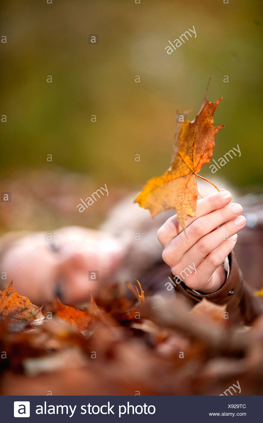 teenage girl lying on ground in autumn holding leaf - Stock Image