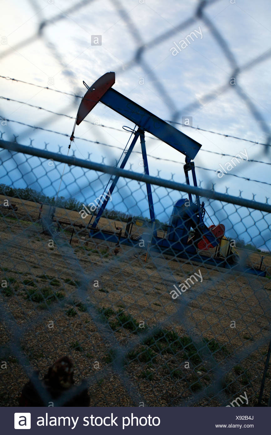 Pump jack behind chain link fence at dusk. - Stock Image