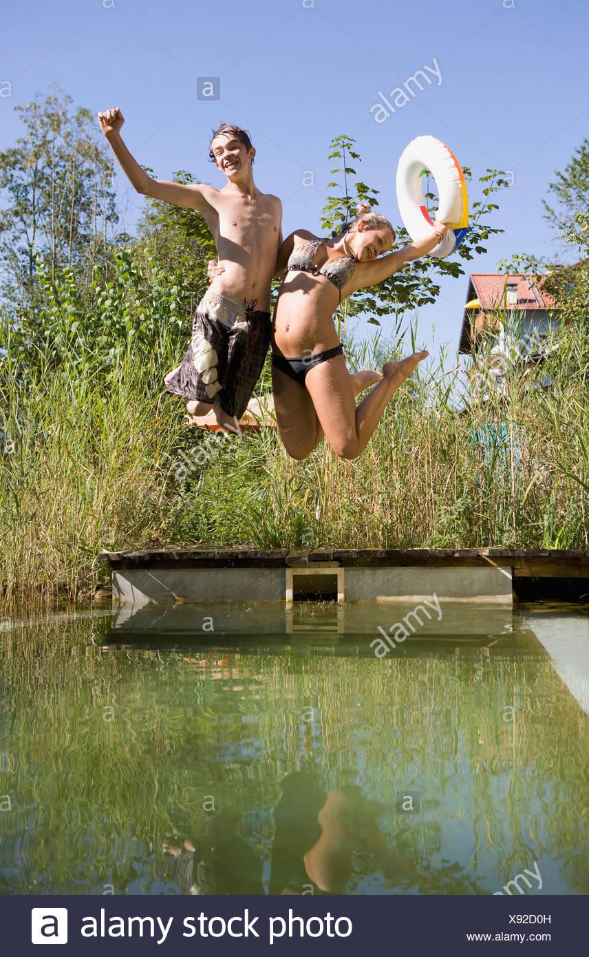 Austria, Salzburger Land, Teenagers (14-15) jumping into lake - Stock Image