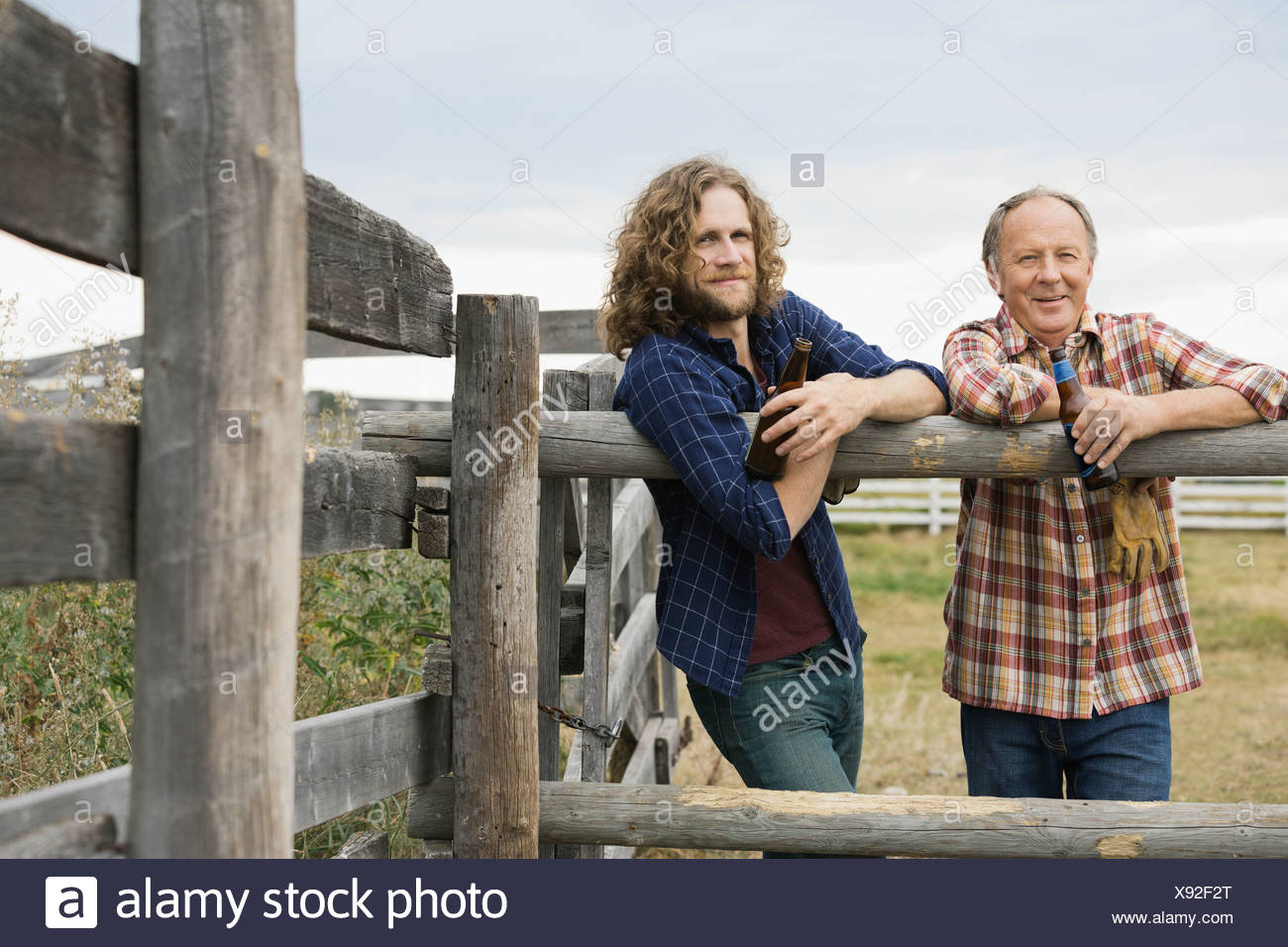 Father and son leaning against farm fence with drinks - Stock Image