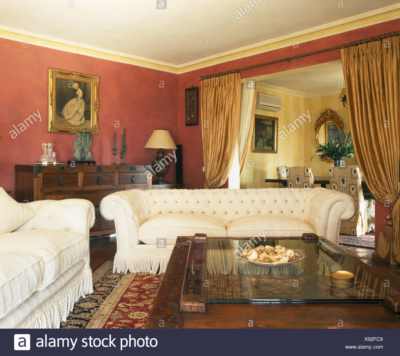 White Sofas And Glass Topped Coffee Table In Red Spanish Living Room With Silk Drapes On Doorway To Dining Room Stock Photo Alamy