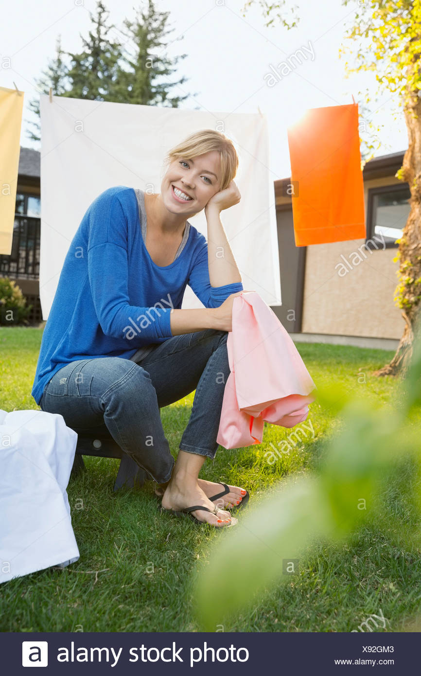 Portrait of woman siting near clothesline in backyard - Stock Image