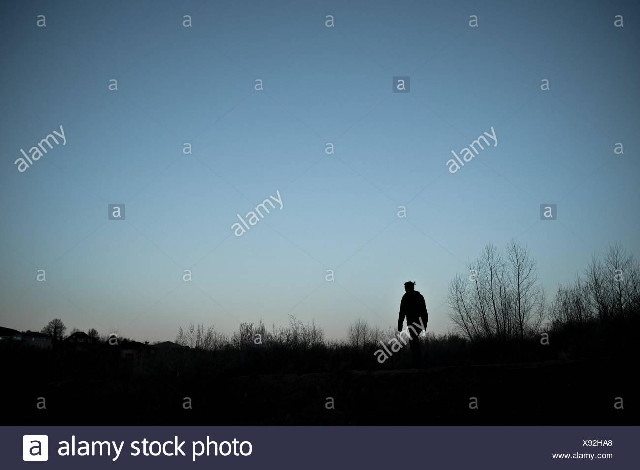 USA, Utah, Silhouette of woman walking at dusk - Stock Image