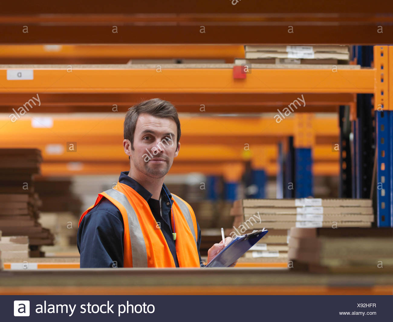Worker In Aisle Of Warehouse Stock Photo