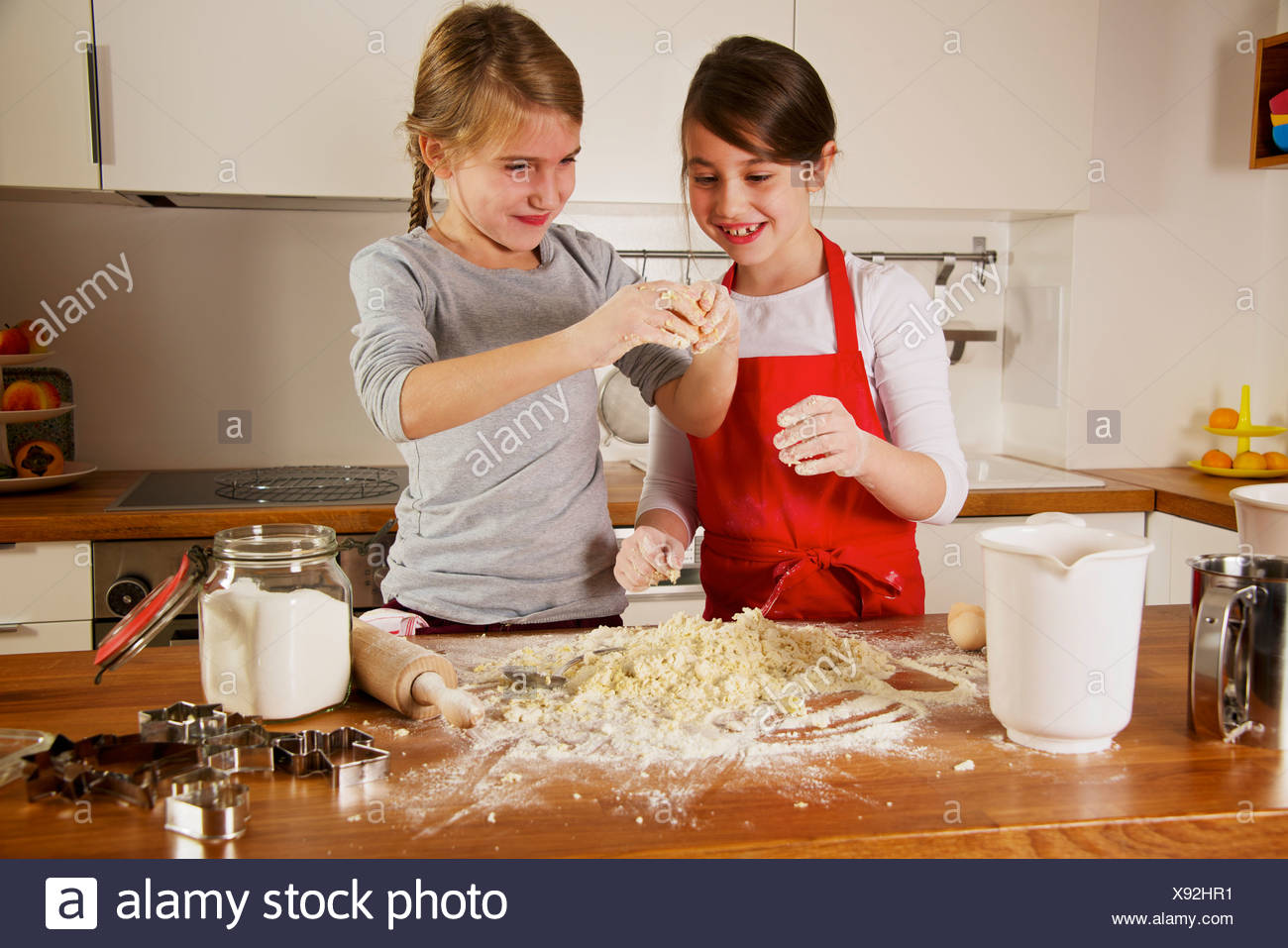 Two girls making Christmas cookies, Munich, Bavaria, Germany - Stock Image