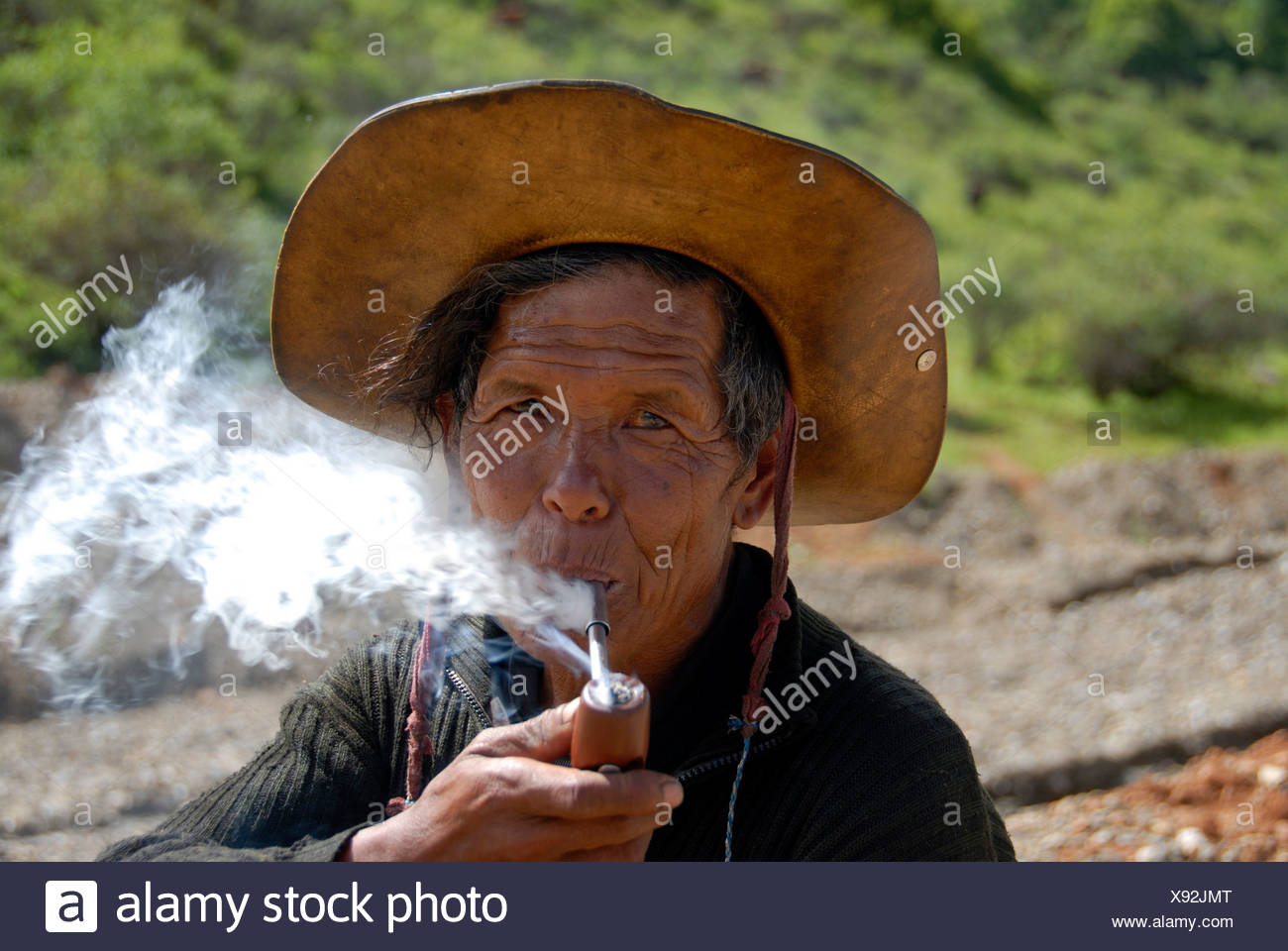 Portrait, ethnology, man of the Mosu ethnicity with hat, smoking a pipe, Yongning, Lugu Hu Lake area, Yunnan Province, People's - Stock Image