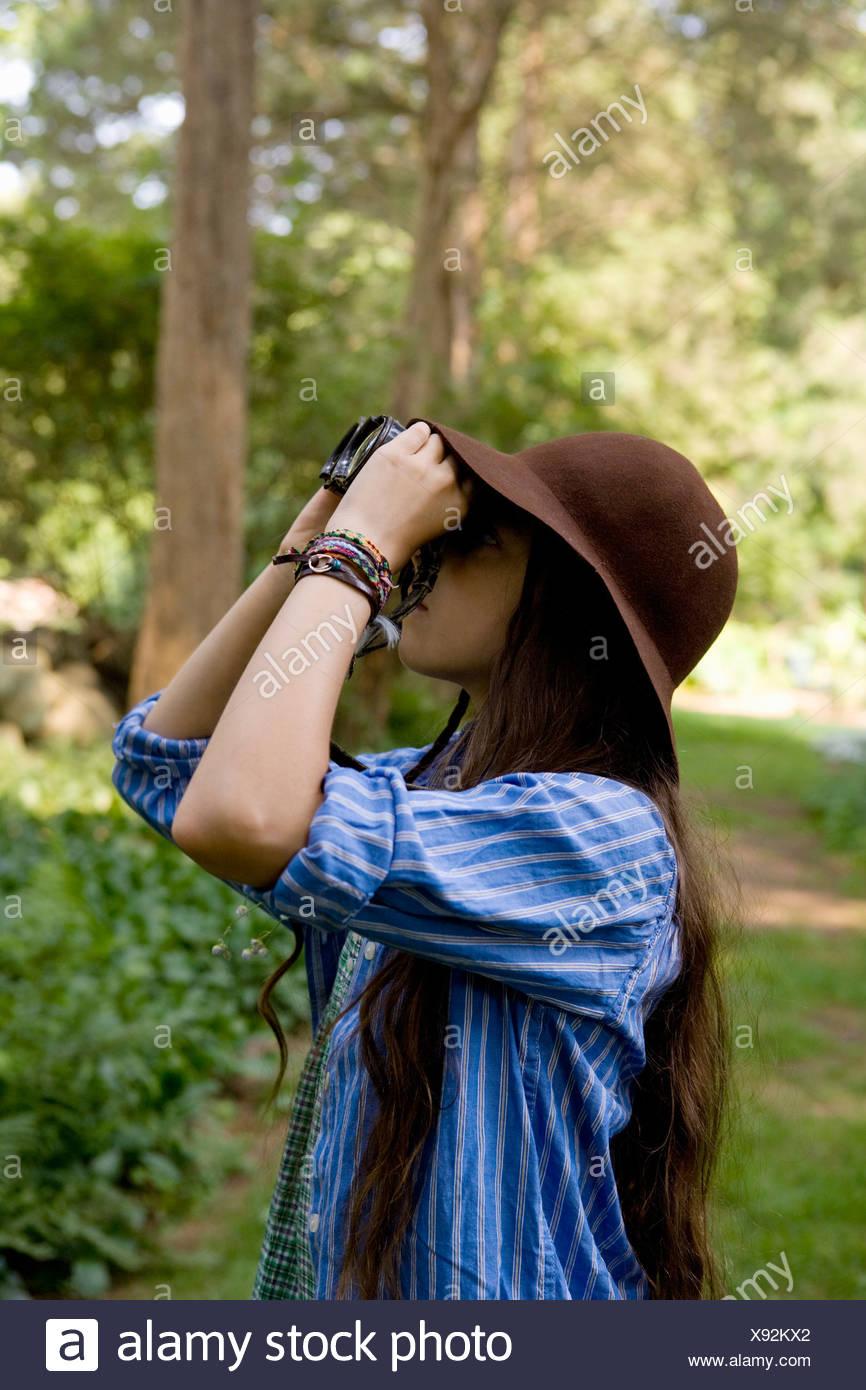 A girl looking through binoculars - Stock Image