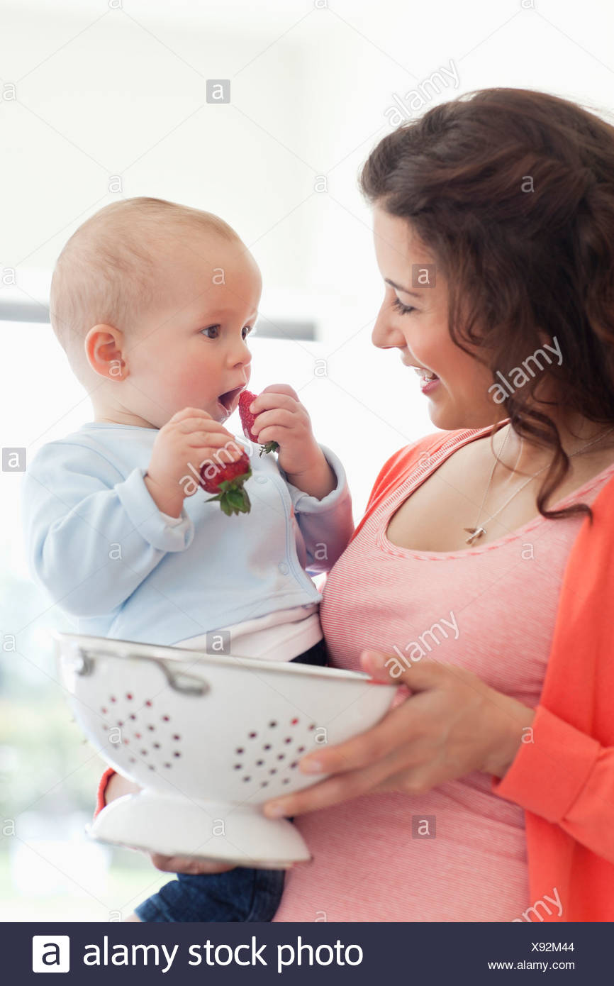 Mother giving baby strawberries - Stock Image