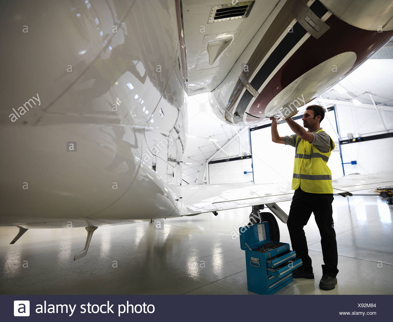 Engineer working on jet aircraft - Stock Image