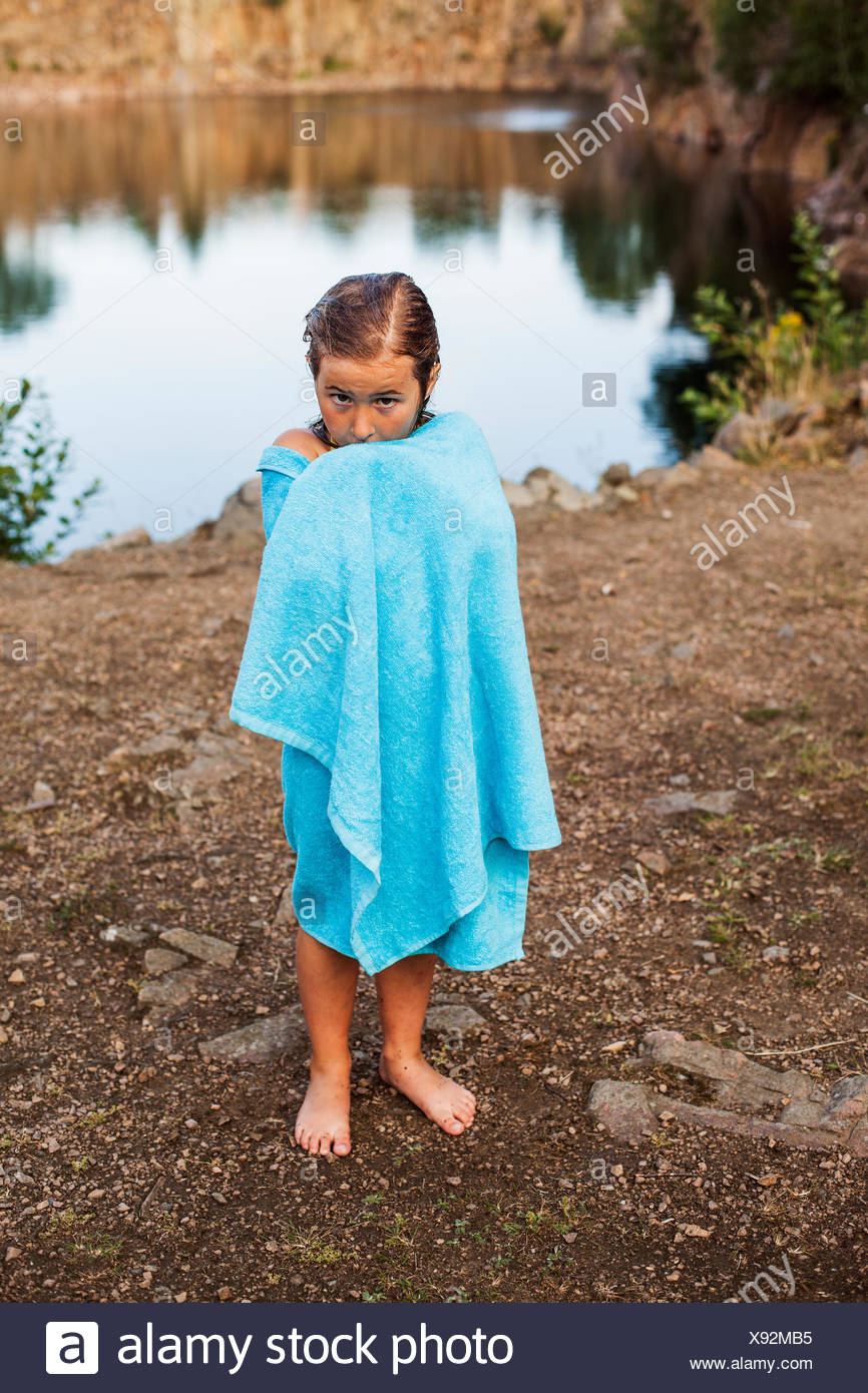 Full length portrait of girl wrapped in towel standing at lakeshore - Stock Image