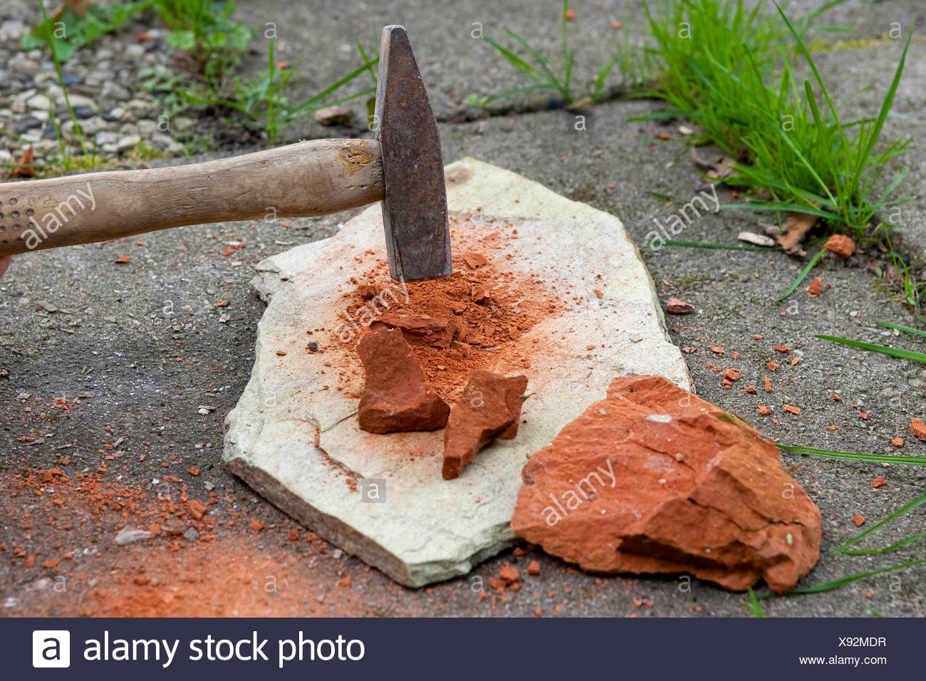 crushing a red sandstone with a hammer to paint with earth colour, Germany - Stock Image