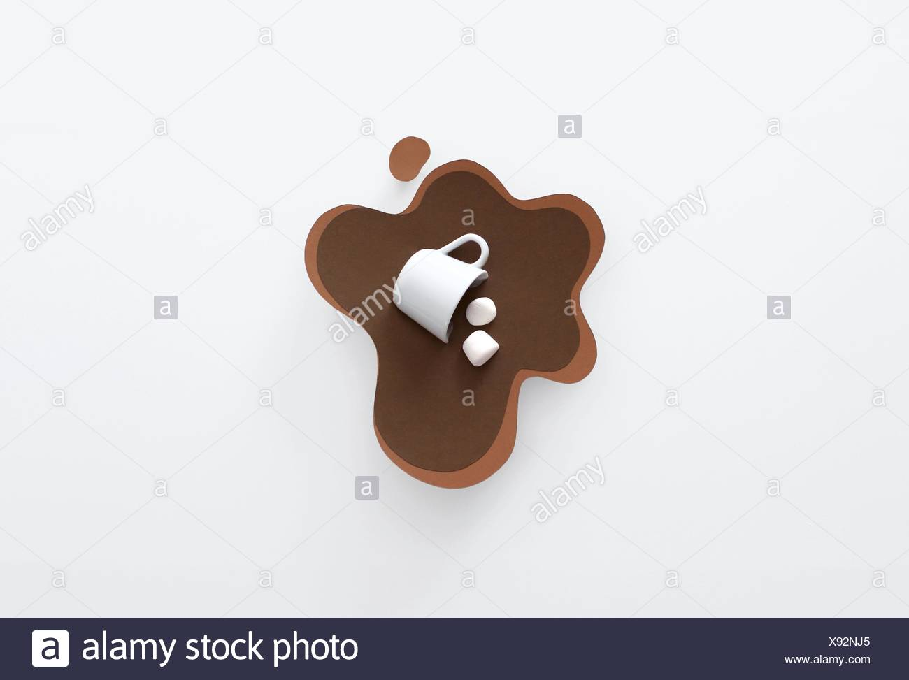 Conceptual mug knocked over, lying in a pool of paper made hot chocolate with marshmallows - Stock Image