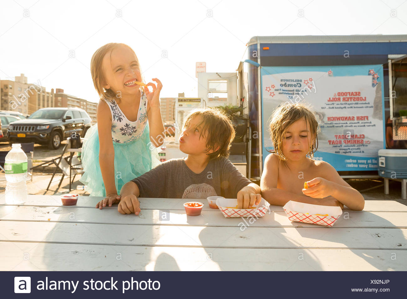 Group of children eating fast food beside fast food trailer - Stock Image