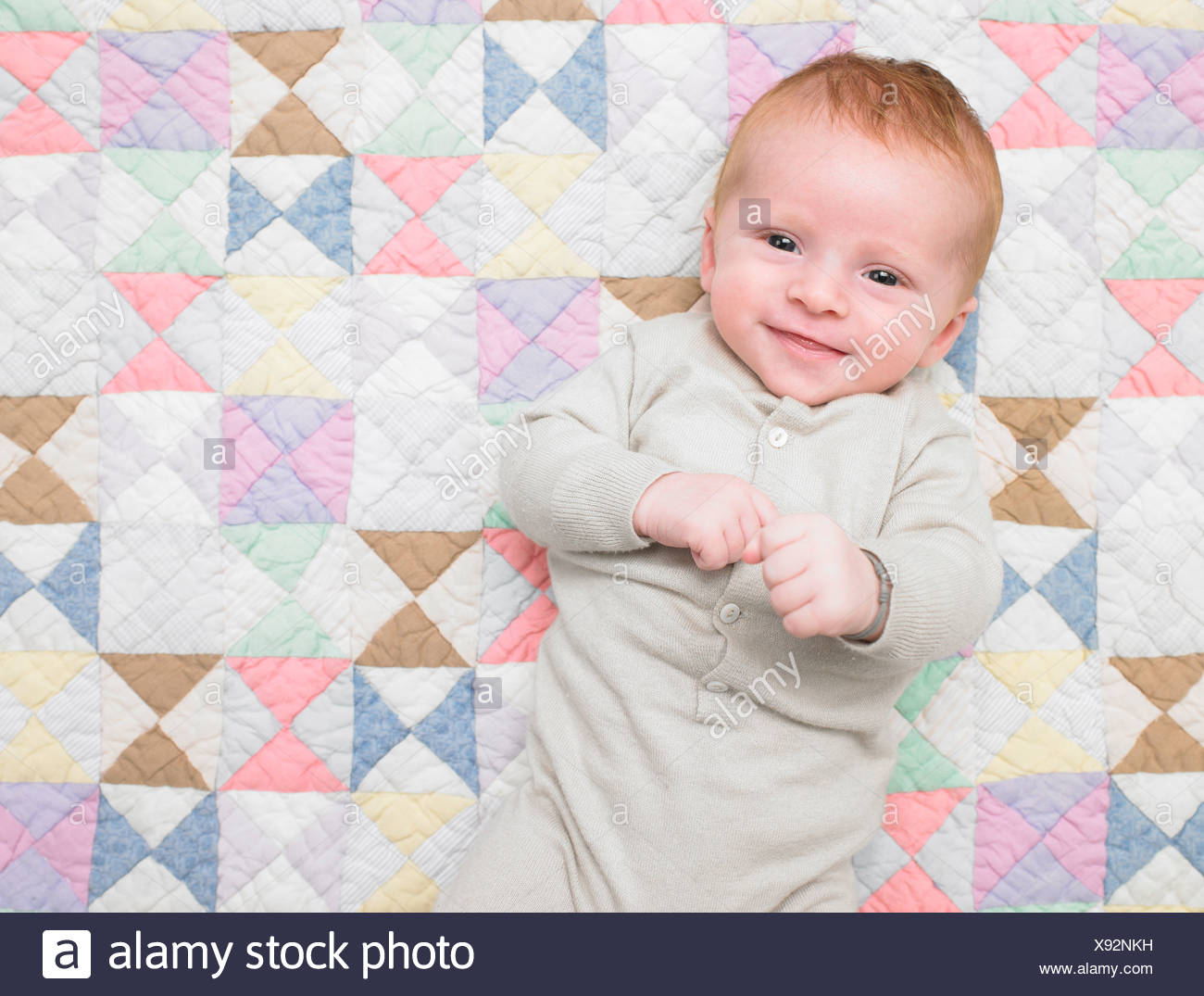 Smiling baby on quilt - Stock Image