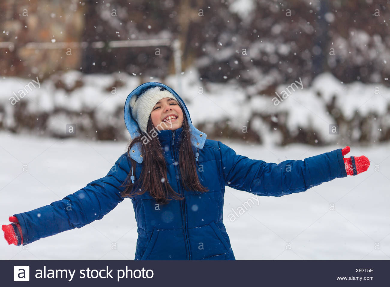 Girl with outstretched arms playing in the snow - Stock Image