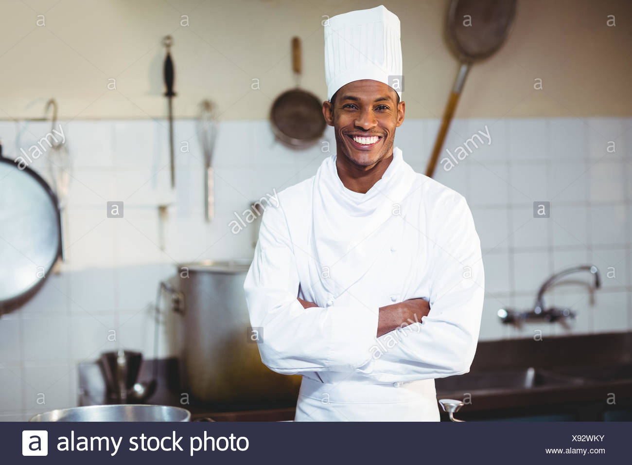 Portrait of happy chef standing with arms crossed - Stock Image