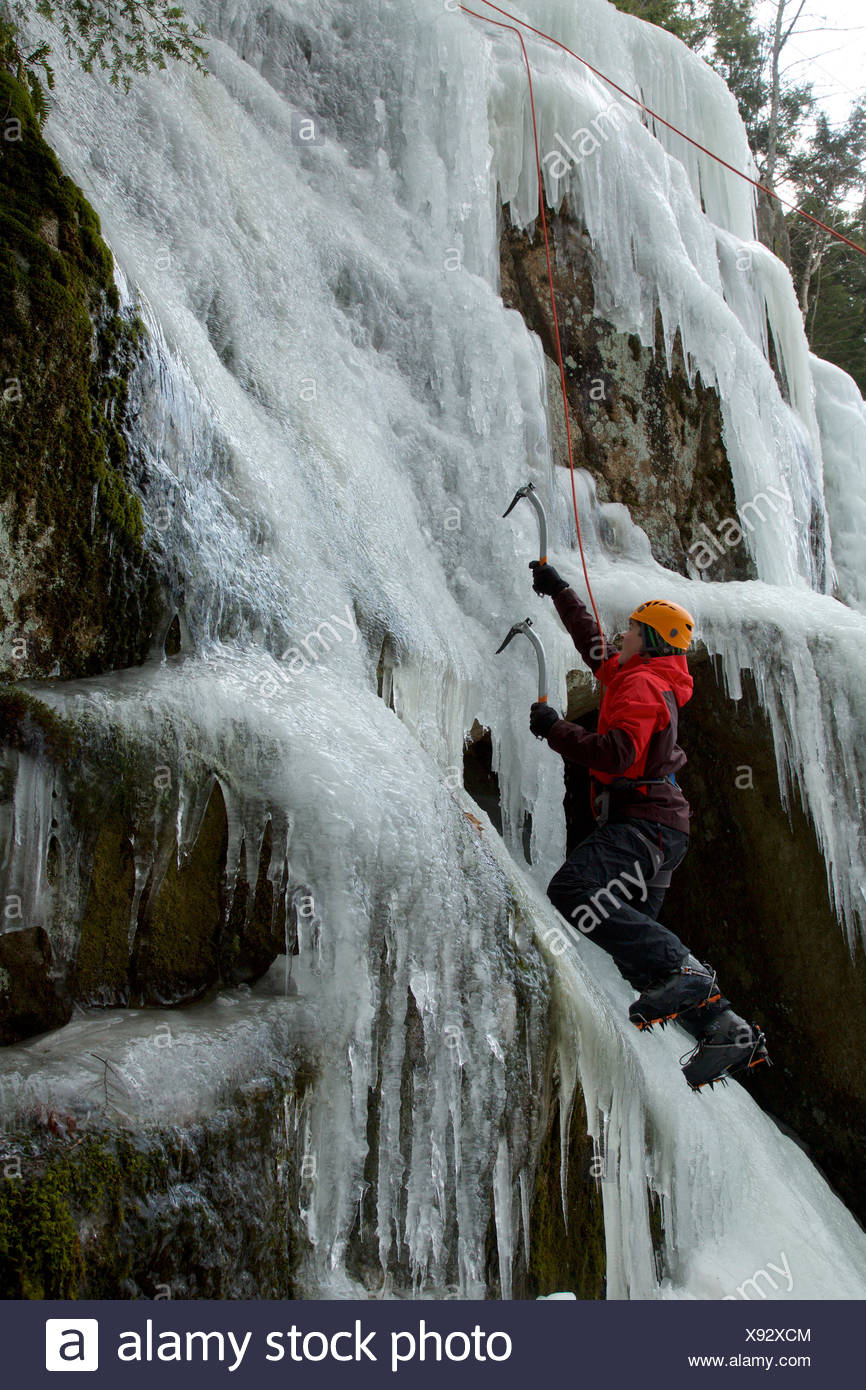 A teen boy ice climbing using ice axes and crampons. Stock Photo