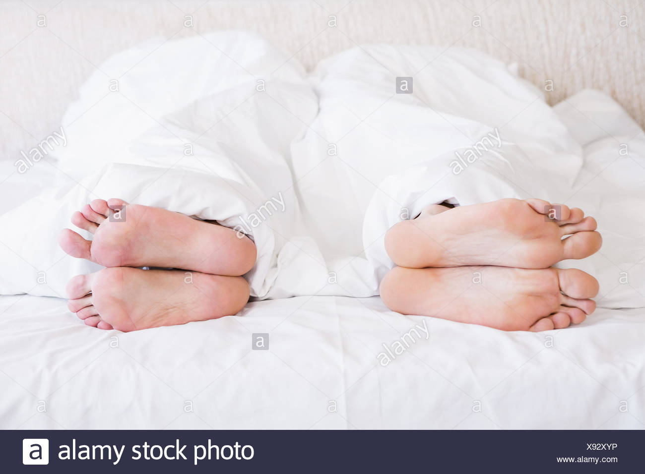 Bare feet of gay couple out from the blanket - Stock Image