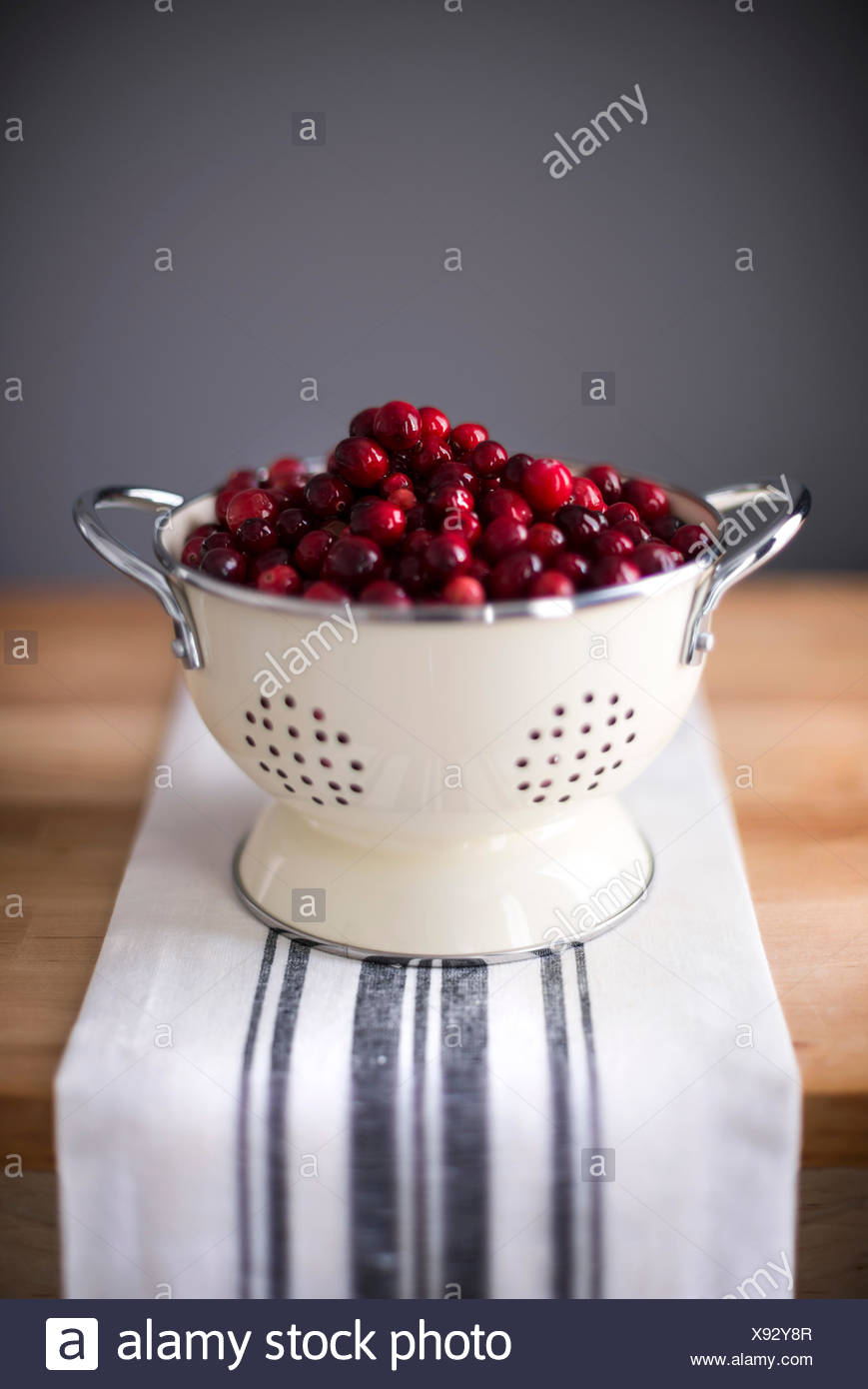 Bright red cranberries in a cream colored strainer. Sitting on a vintage striped linen on butcher block. - Stock Image