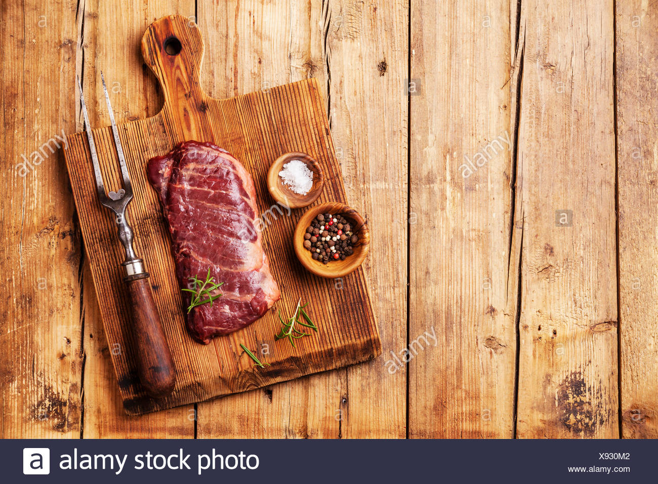Raw fresh meat Steak Machete with salt and pepper on wooden background - Stock Image