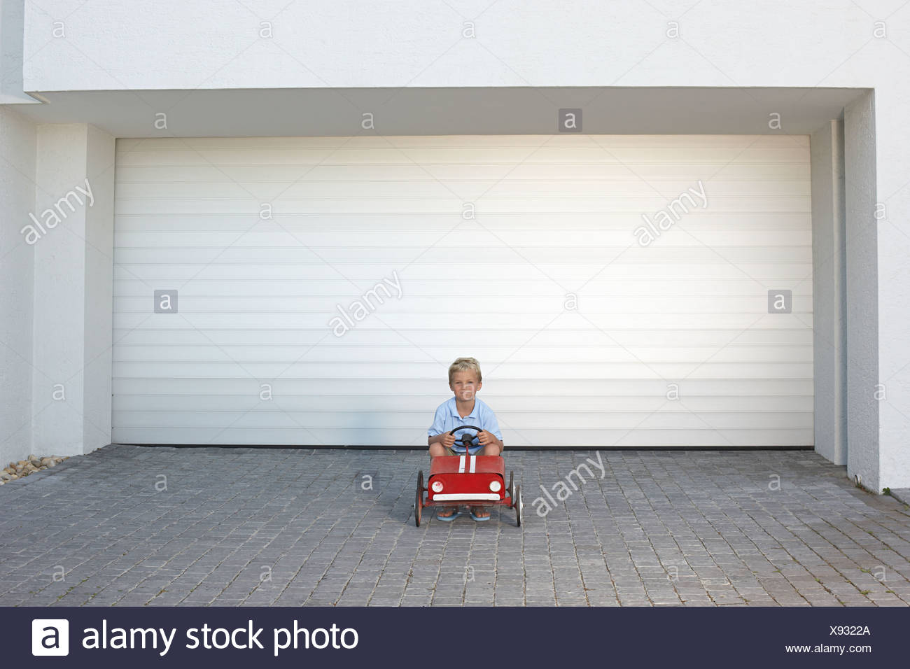 Young boy sat in a toy car - Stock Image