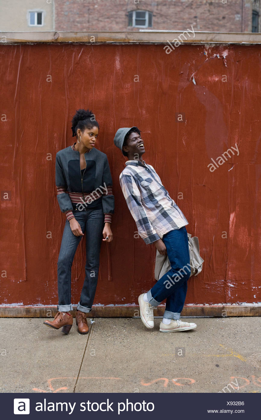 A young couple standing on a sidewalk - Stock Image