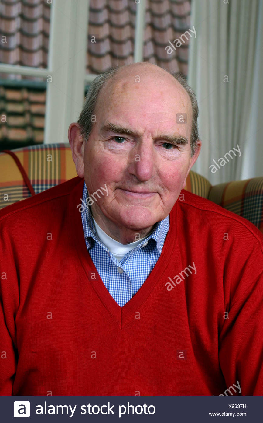 Retired man sit on arm chair - Stock Image