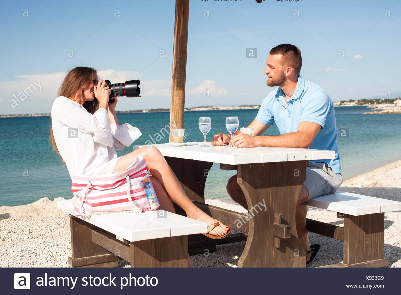 Young woman at beach bar taking photos of friend Stock Photo