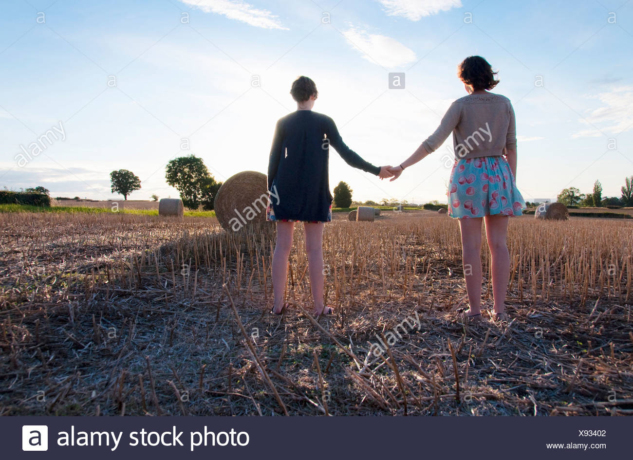 Girls holding hands in hay field - Stock Image