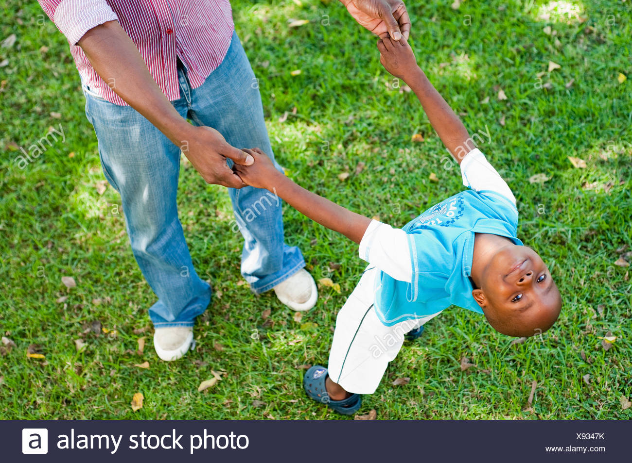Boy (4-5) playing with father on lawn in garden, Johannesburg, Gauteng Province, South Africa - Stock Image