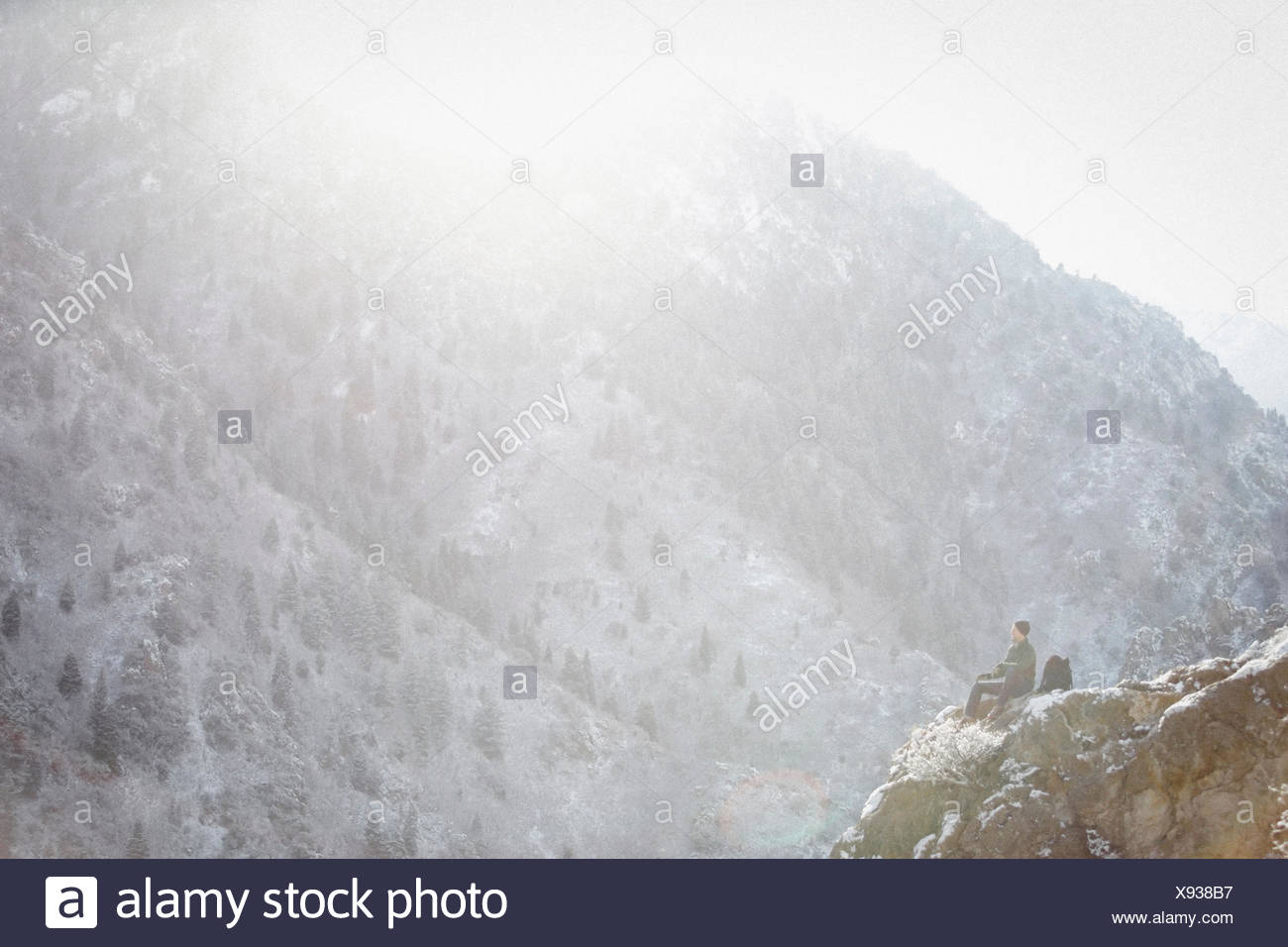 A man, a hiker in the mountains, taking a rest on a rock outcrop above a valley. - Stock Image