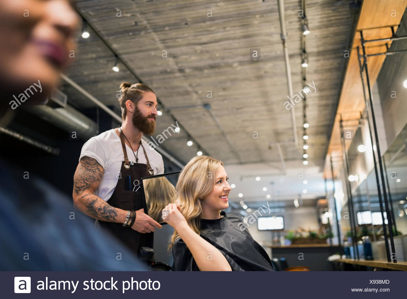 Hairstylist showing woman hair with mirror hair salon - Stock Image