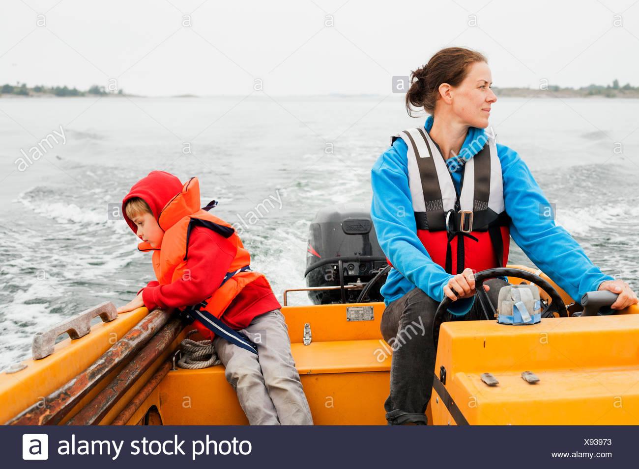 Sweden, Uppland, Runmaro, Barrskar, Mother and son (4-5) on motor boat - Stock Image