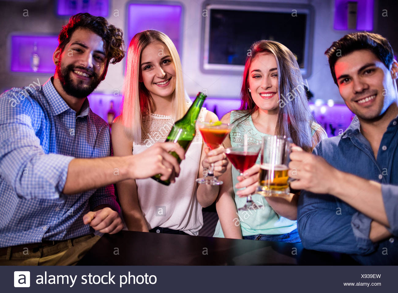Group of friends toasting cocktail, beer bottle and beer glass at bar counter Stock Photo