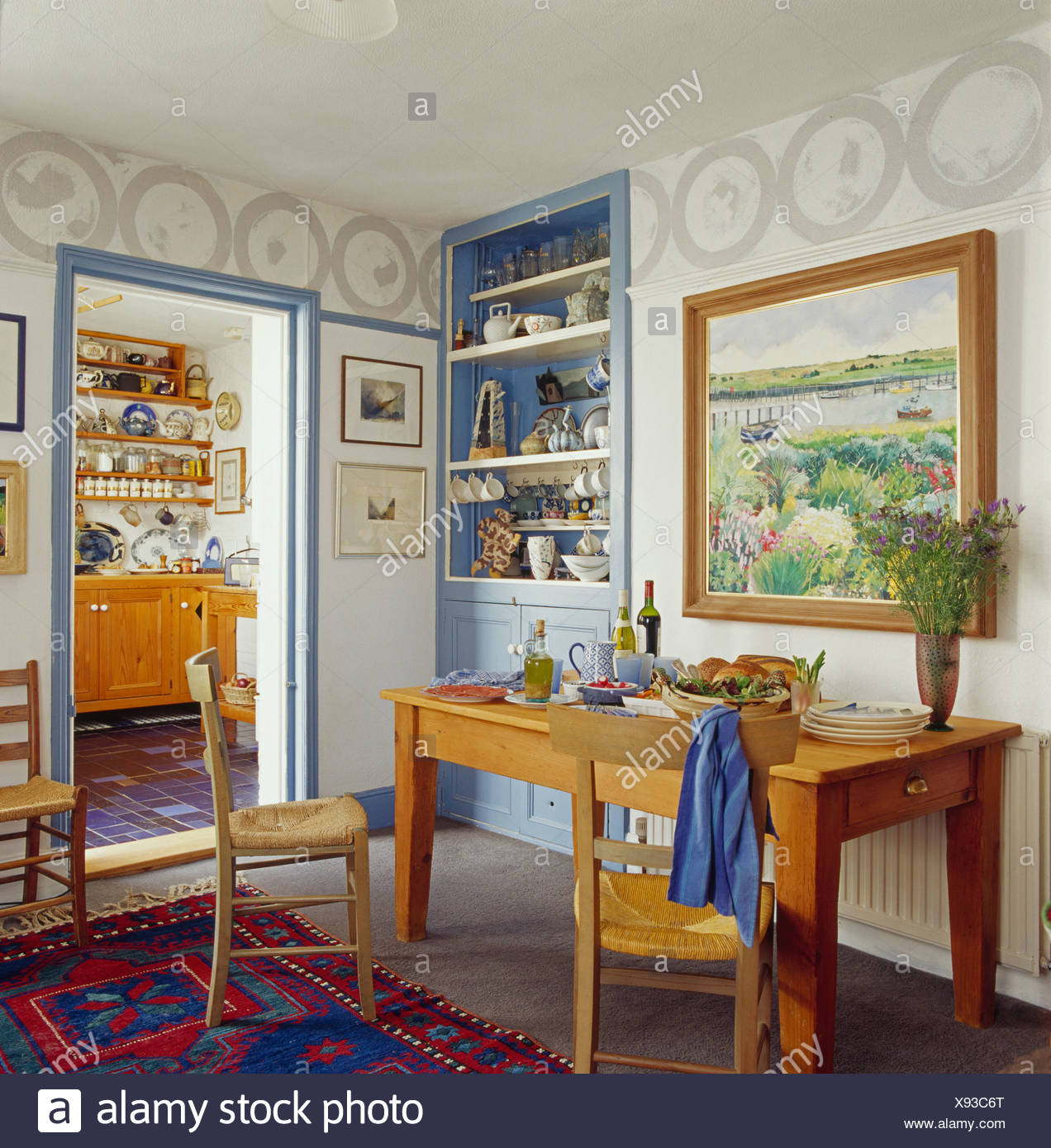 Large Picture On Wall Above Narrow Pine Table Set For Lunch In Cottage Dining  Room With Blue Alcove Shelves And Painted Border