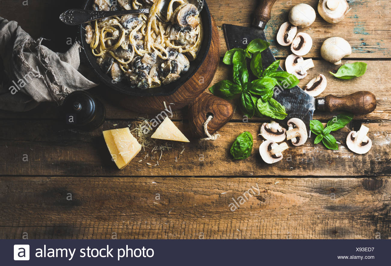 Italian style dinner. Creamy mushroom pasta spaghetti in cast iron pan with Parmesan cheese, fresh basil and pepper over old rus - Stock Image