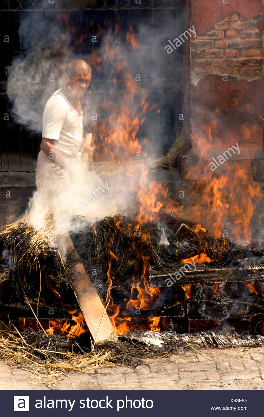 Traditional funeral, untouchable priest of the lowest caste tending pyre, Pashupatinath, Nepal, Asia - Stock Image